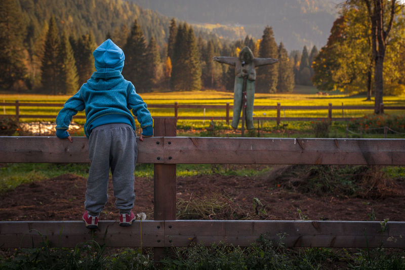 Rear view of boy standing on fence against field