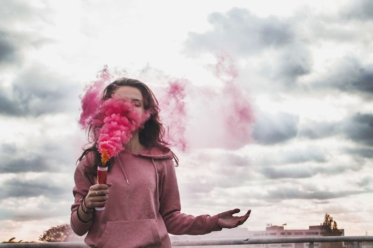 Low angle view of young woman holding smoke bomb while standing against cloudy sky