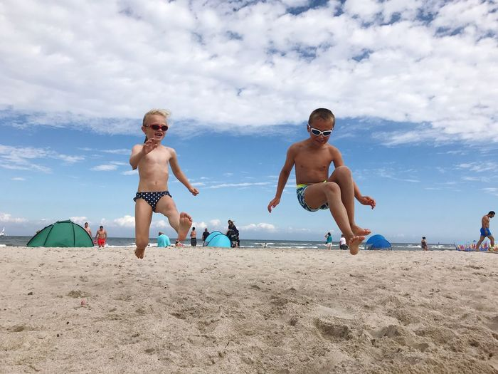 Siblings Jumping On Sand At Beach Against Sky