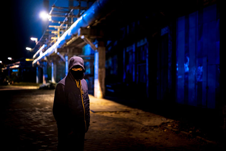 One Person Night Architecture Illuminated Building Exterior Real People Built Structure Lifestyles Standing Building Leisure Activity City Clothing Men Adult Hood Focus On Foreground Rear View Street Hood - Clothing Warm Clothing Dark Criminal Fear Eyes