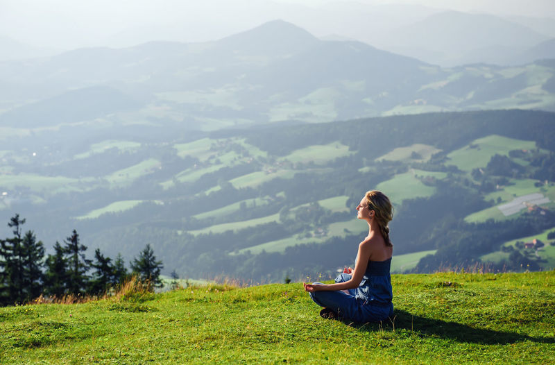 Woman meditating on grass over mountain