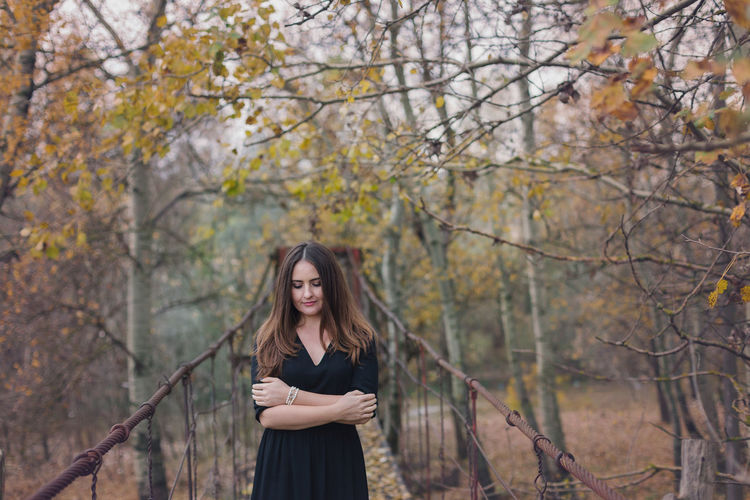 Young woman standing by trees in park