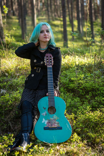 Hipster young woman with turquoise guitar sitting in forest