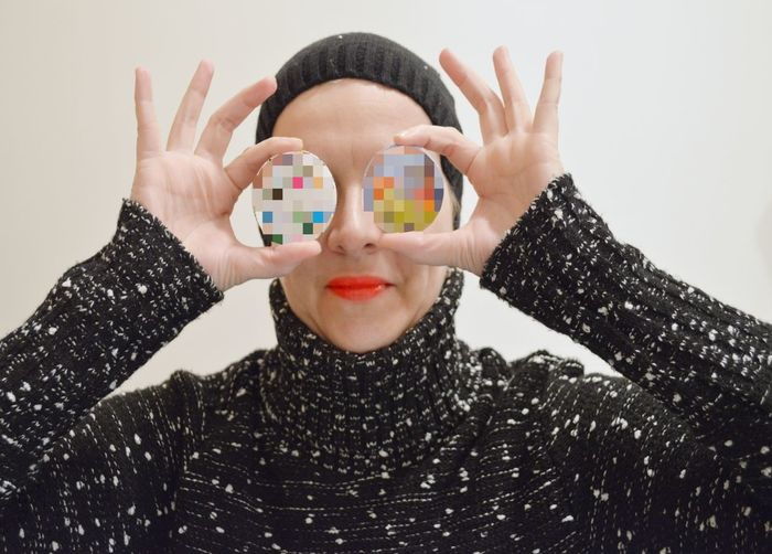 Close-Up Of Woman In Costume Covering Eyes With Multi Colored Objects Against White Background