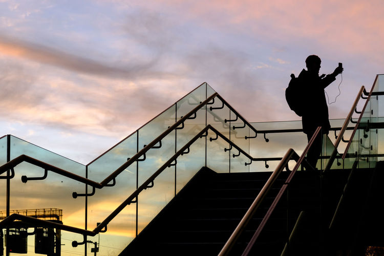 Low angle view of silhouette man standing on staircase