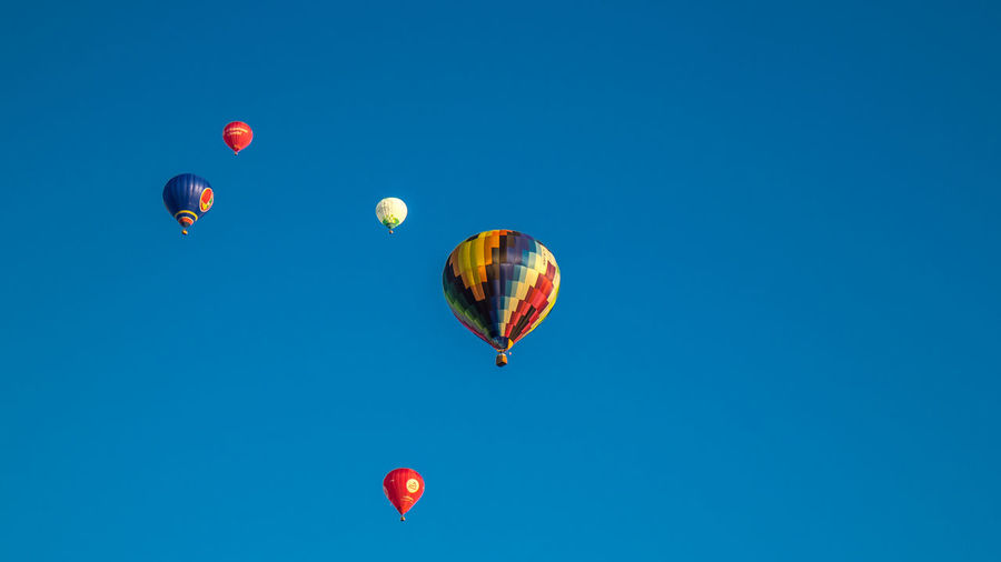 Low angle view of hot air balloons in clear blue sky