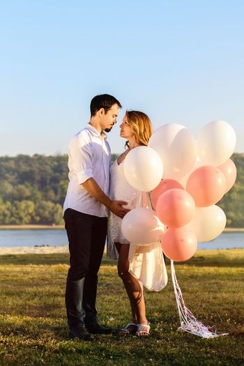 Balloons Beach River Rose And White Color White Dress Pregnant Woman Pregnant Belly  Pregnant Phtography Pregnancy Balloons Couples Couple Balloon Celebration Sky Standing Full Length Nature Holding Positive Emotion Emotion Outdoors Field Event EyeEmNewHere