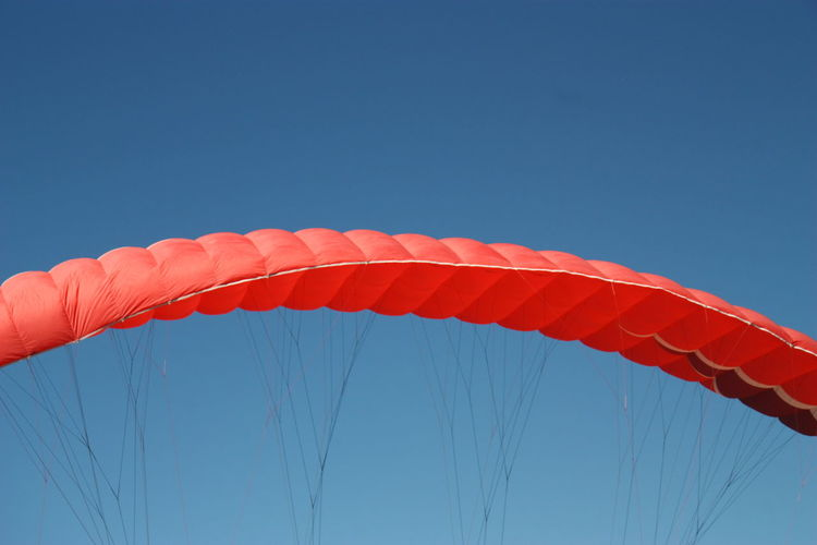 Low angle view of woman flying against clear blue sky