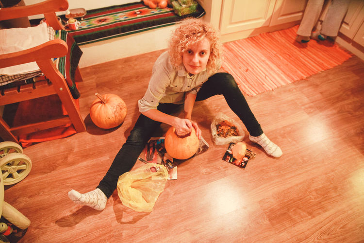 High angle portrait of woman carving pumpkin at home