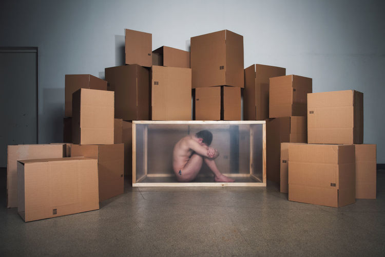 Naked mid adult man sitting in container by cardboard boxes at home