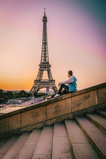 Side View Of Man Sitting Against Eiffel Tower And Dramatic Sky In City