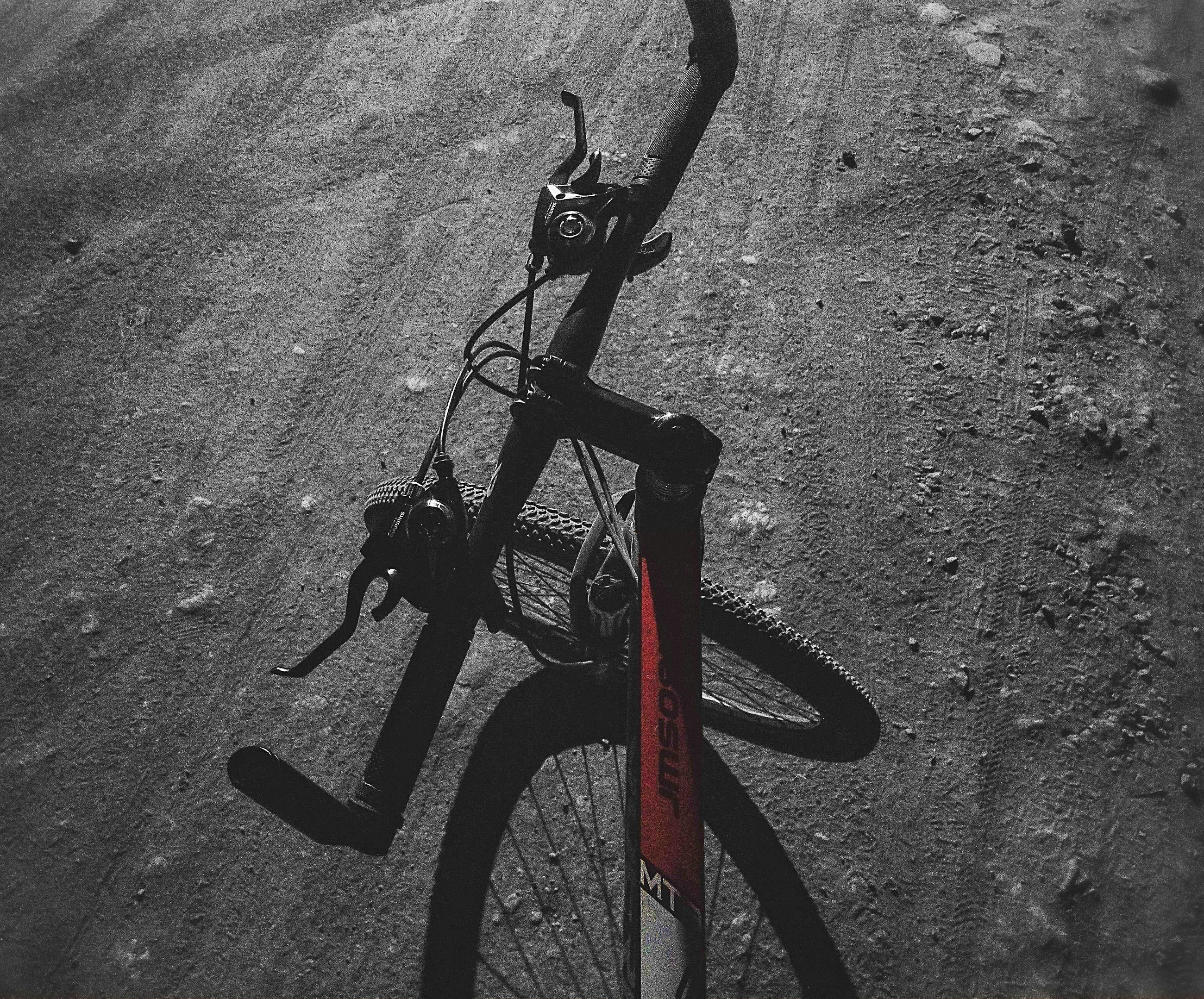 bicycle, transportation, land vehicle, mode of transportation, stationary, no people, high angle view, day, street, road, shadow, sunlight, outdoors, metal, nature, city, footpath, parking, wall - building feature, close-up