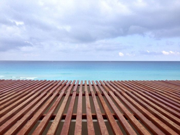 Scenic view of pier over sea against cloudy sky