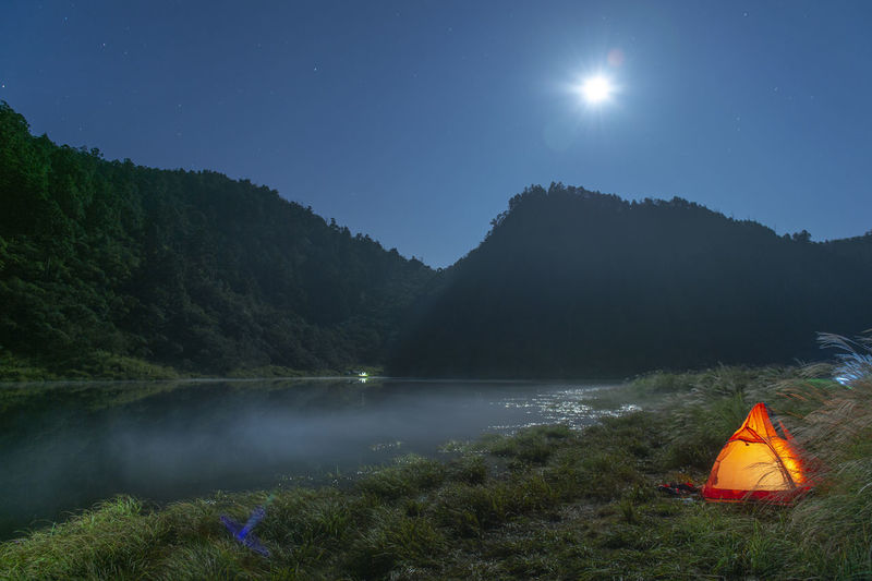 Tent on mountain by lake against sky at night