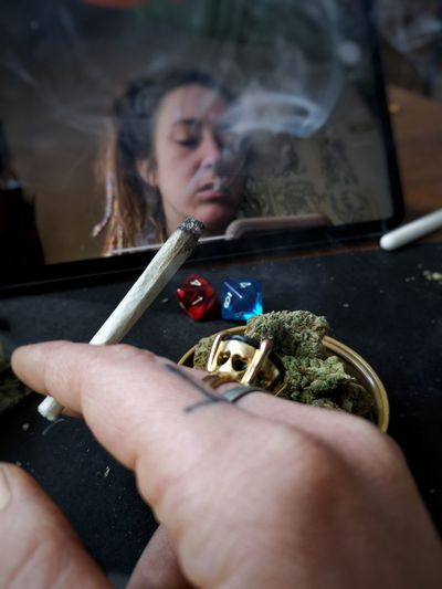 Reflection of close-up of woman holding weed spliff with dices and weed flowers
