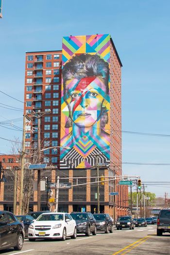 KobraStreetArt Kobra Street Art David Bowie Architecture Car Motor Vehicle Mode Of Transportation Transportation Sky Built Structure Building Exterior Land Vehicle Travel Destinations Travel Outdoors Multi Colored No People Flag City Life City Nature Street Day