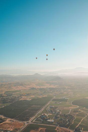 Aerial view of hot air balloon against clear blue sky