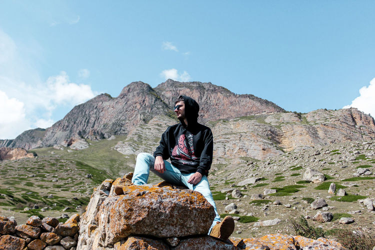 Full length of man sitting on rock against mountains