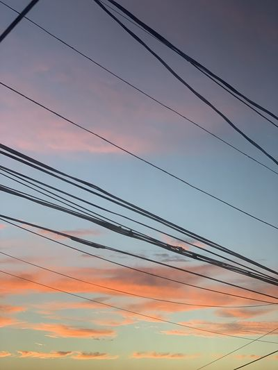 Low angle view of power lines against sky at sunset