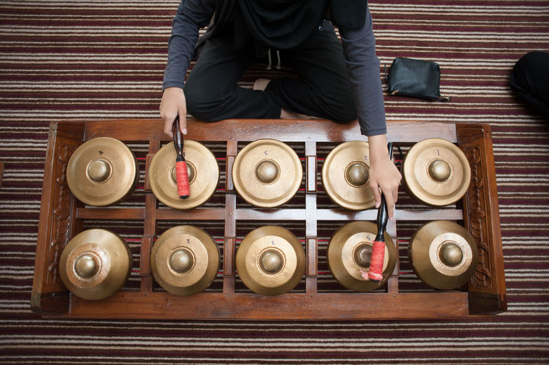 Midsection Of Women Playing Gamelan On Floor