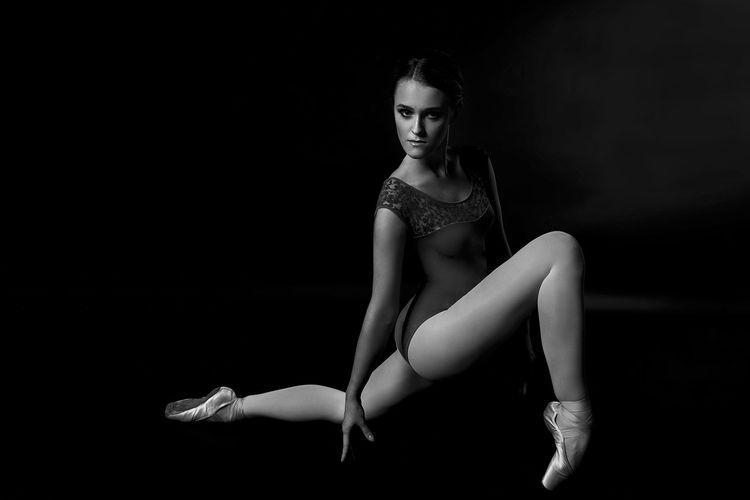 Portrait of ballet dancer stretching against black background