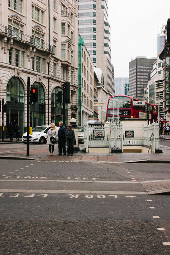 People waiting for the lights to turn green in a street in London, UK. Architecture Building City City Life City Street England London Outdoors Road Traffic Traffic Lights United Kingdom