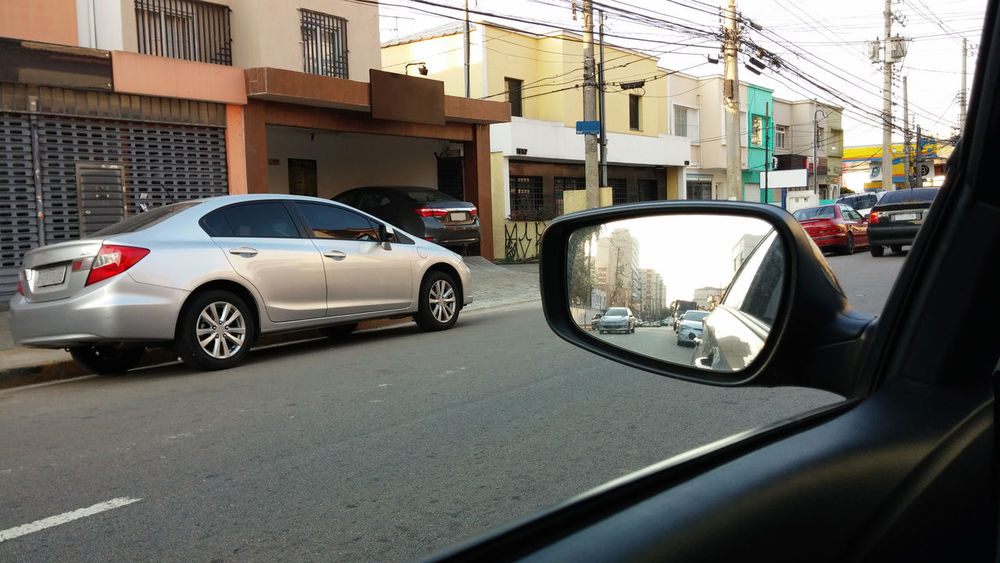The reflection of cars an buildings in the city in the rearview mirror of the car Asphalt City Mirror Rear View Reflection Travel Building Exterior Car City Day Drive Mode Of Transport No People Outdoors Rear View Mirror Road Side-view Mirror Street Transportation