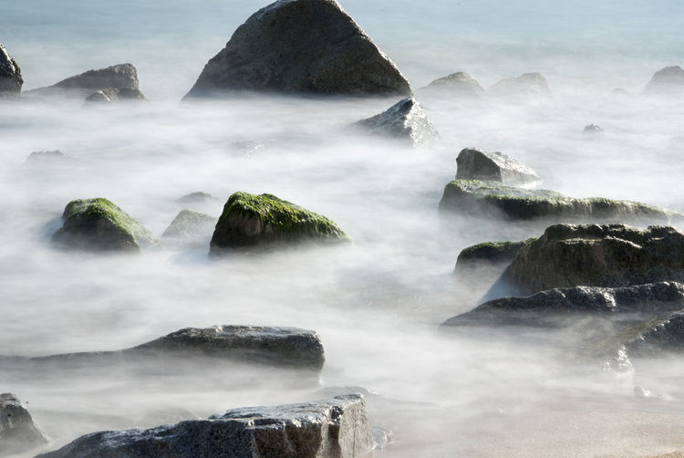 View of rocks at beach in foggy weather