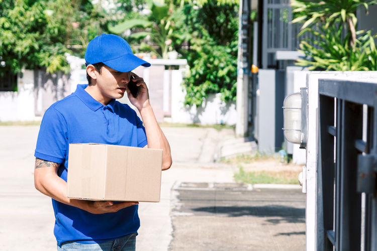 Salesman carrying box while talking on phone by gate