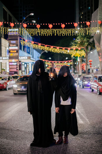 Rear view of couple standing on illuminated street at night