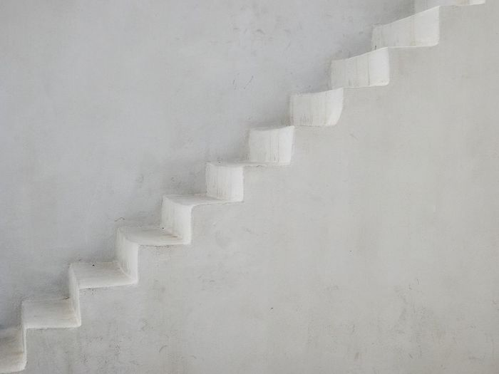 Empty steps by white wall