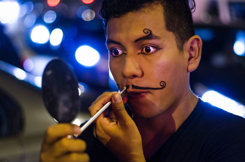 Man painting mustache on face against illuminated light during night