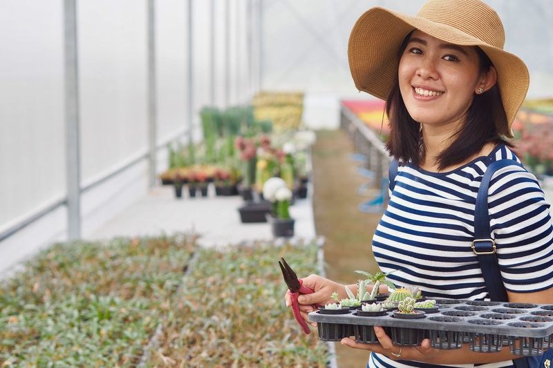 Portrait Of Smiling Woman Holding Seedling Tray In Greenhouse