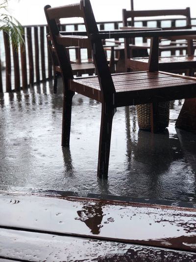 Empty chairs and table on floor during rainy season