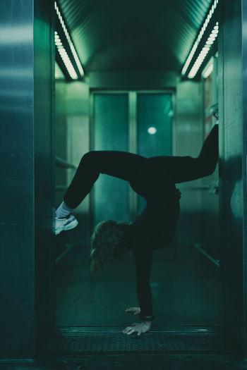 Full length of woman exercising in dark corridor