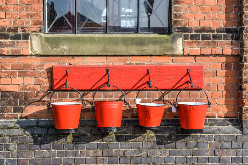Four fire buckets hung up on exterior brick wall. Fire Buckets Industrial Architecture Brick Brick Wall Building Exterior Built Structure Day Firefighting Equipment Man Made Object No People Outdoors Windows