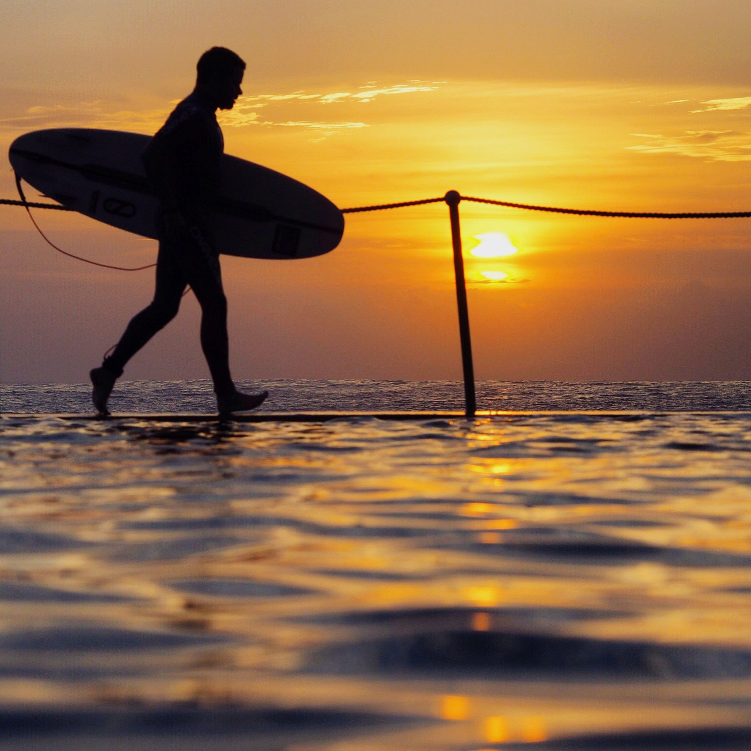 sunset, sea, water, scenics, sun, horizon over water, idyllic, silhouette, tranquil scene, tranquility, full length, beauty in nature, sky, reflection, motion, nature, orange color, surface level, cloud - sky, remote, dramatic sky, enjoyment, hobbies, vacations, holding, outdoors, fun, majestic, moody sky, carefree, mountain
