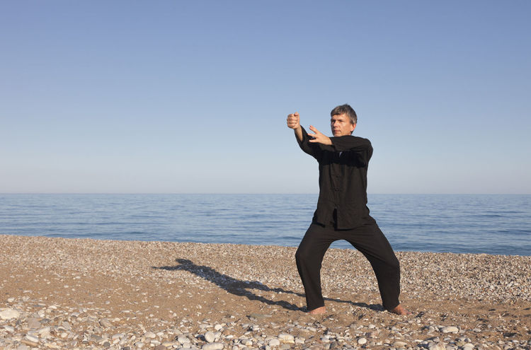 Man practicing Tai Chi – Posture Fist Exercising Man Martial Arts Tai Chi Tai Chi Chuan Taiji Arms Outstretched Arms Raised Barefoot Beach Front View Full Length Healthy Lifestyle Mature Men One Man Only One Mature Man Only One Person Outdoors Practicing Sea Sport Sports Clothing Taichi Taijiquan Zen