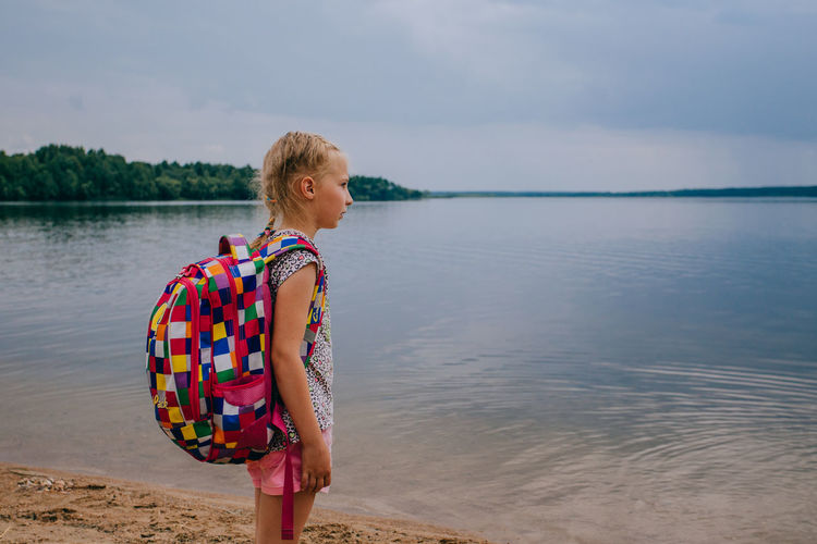 Girl Wearing Backpack While Standing At Beach Against Sky