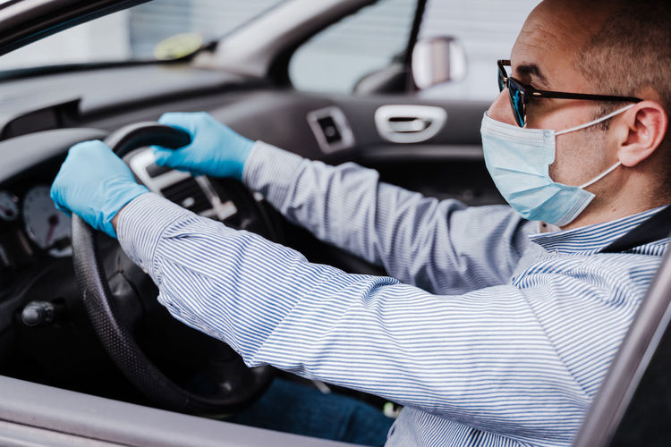 Close-up of man wearing mask sitting in car