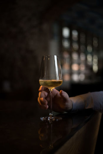 Cropped image of man hand holding wineglass at bar counter