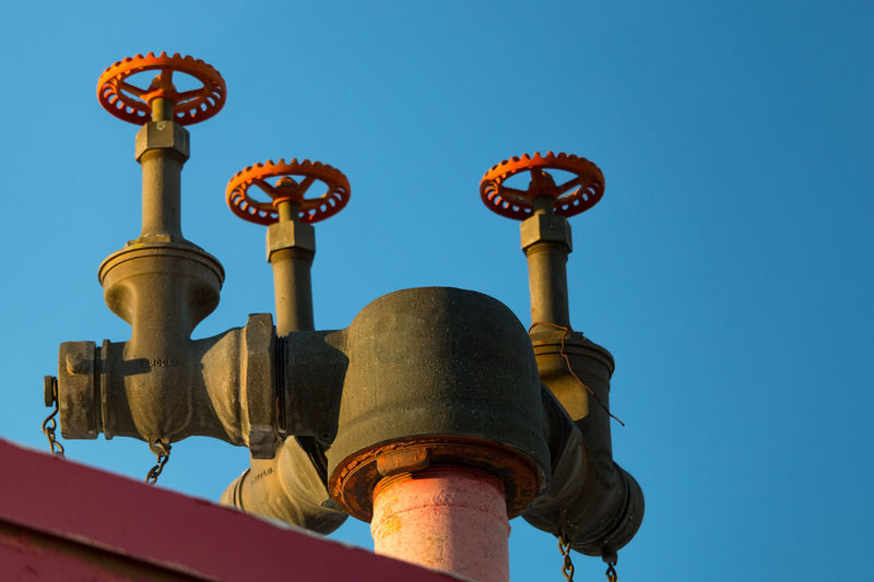 Low angle view of water pipe gauge against blue sky