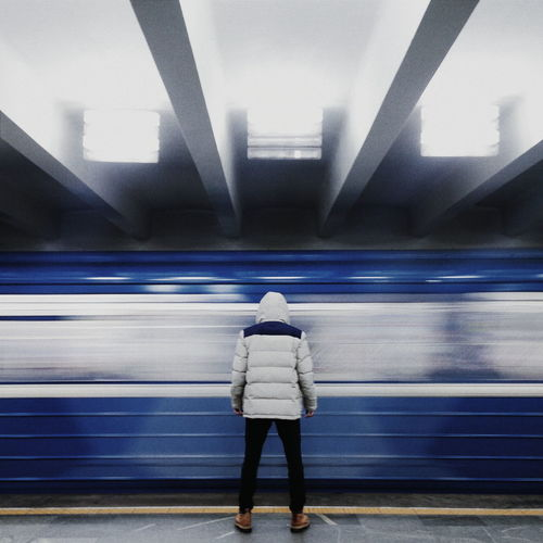 Rear view of man standing against train at railroad station