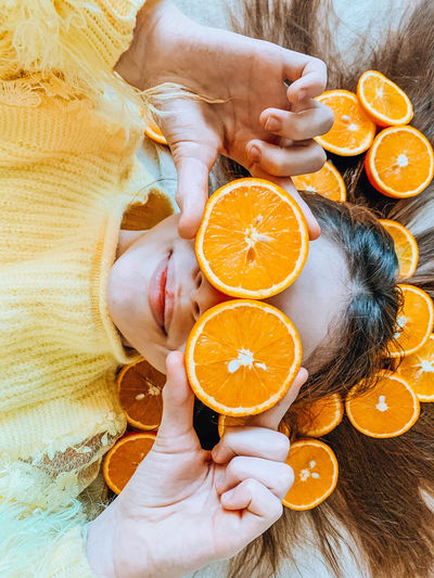 High angle view of woman holding orange fruit