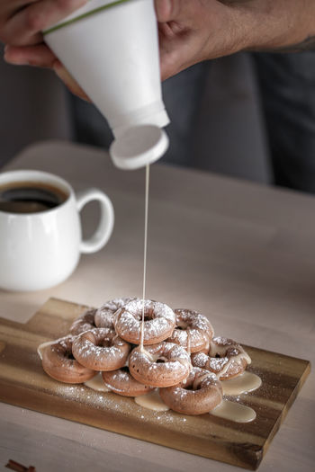 Cropped Image Of Man Pouring Caramel On Donuts In Kitchen