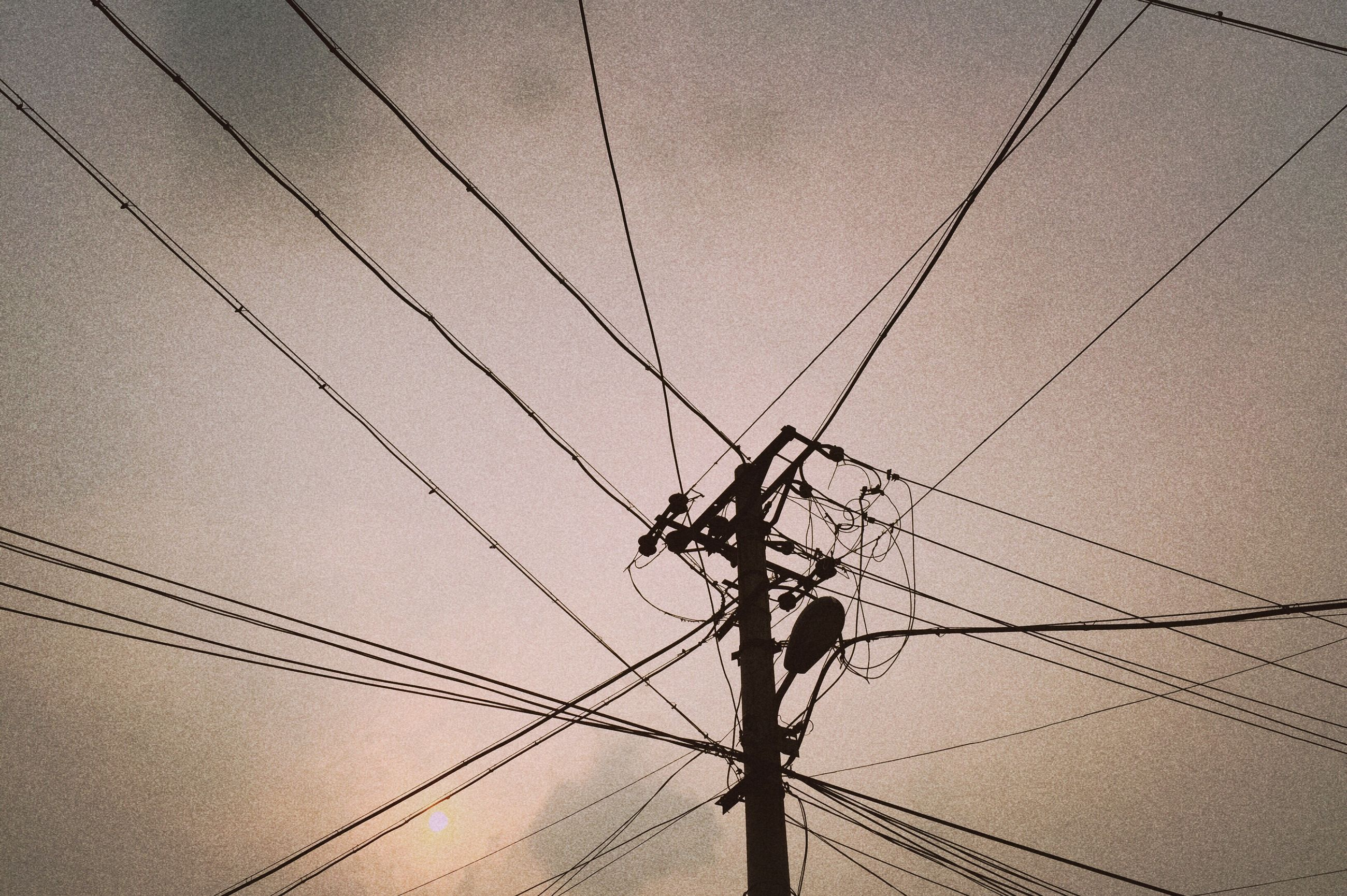 power line, power supply, electricity, low angle view, electricity pylon, connection, cable, fuel and power generation, technology, complexity, sky, power cable, silhouette, built structure, outdoors, no people, day, architecture, backgrounds, wire