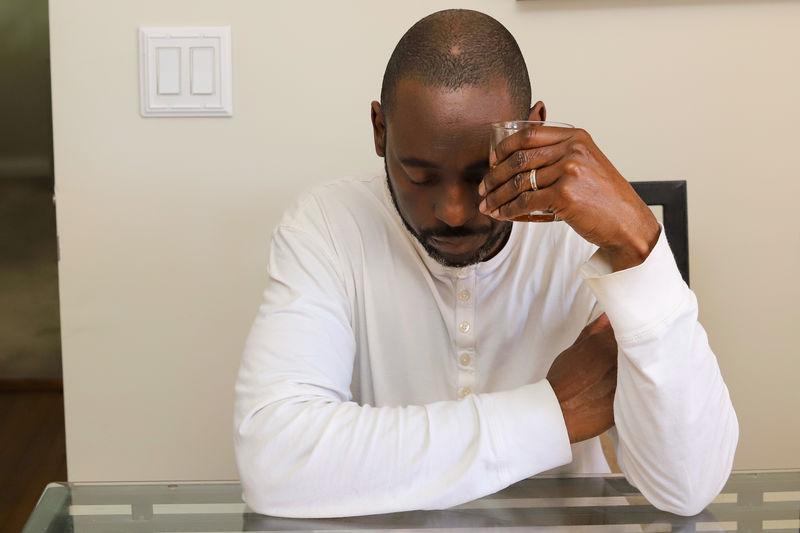 Man looking at camera while sitting on wall at home
