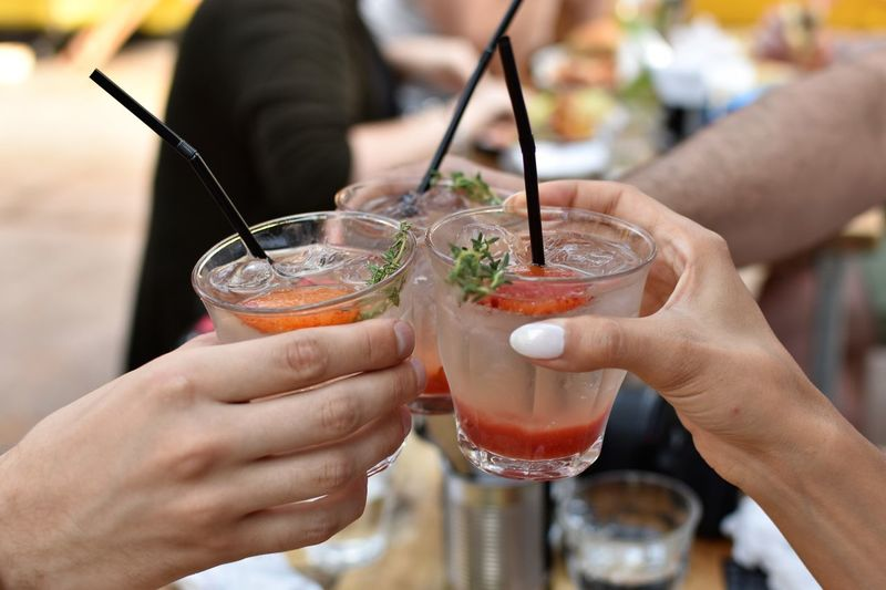 Cropped hands of friends toasting drinks