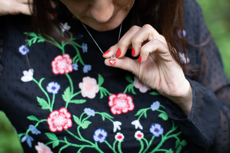 High angle view of woman hand holding red flowering plants