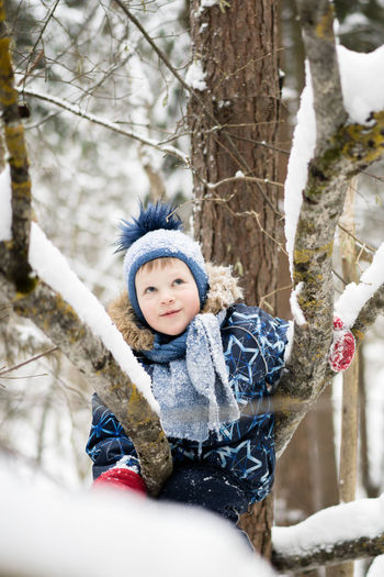 Boy Lying On Tree Trunk During Winter
